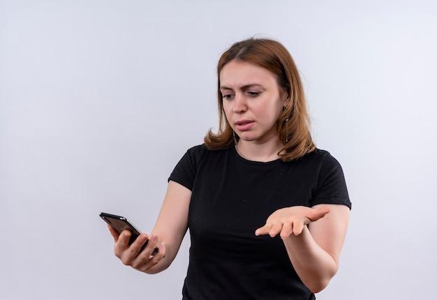 Giovane donna casuale confusa che tiene il telefono cellulare e che mostra la mano vuota sullo spazio bianco isolato con lo spazio della copia