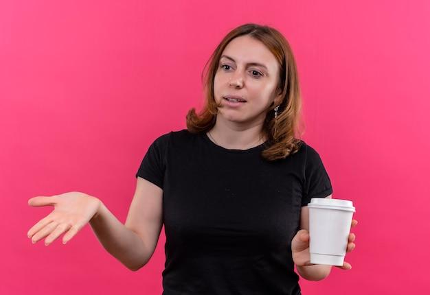 Giovane donna casuale confusa che tiene la tazza di caffè di plastica e che mostra la mano vuota sullo spazio rosa isolato