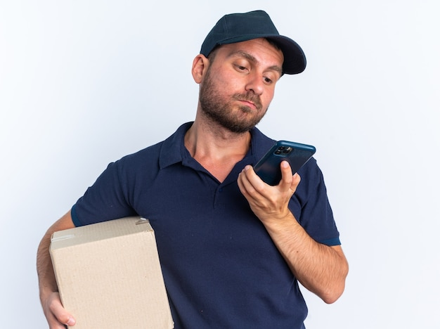 Confused young caucasian delivery man in blue uniform and cap holding cardboard box and mobile phone looking at mobile phone isolated on white wall