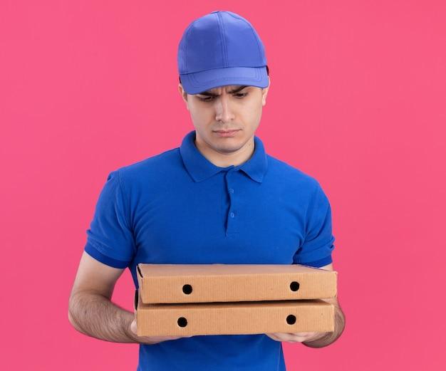 Confuso giovane fattorino caucasico in uniforme blu e berretto che tiene in mano e guarda i pacchetti di pizza