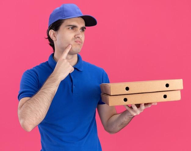 Confuso giovane fattorino caucasico in uniforme blu e cappuccio che tiene i pacchetti di pizza mettendo il dito sul viso guardando a lato