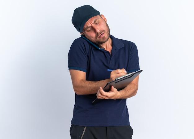 Confuso giovane fattorino caucasico in uniforme blu e berretto parlando al telefono scrivendo negli appunti con penna isolata sul muro bianco con spazio di copia
