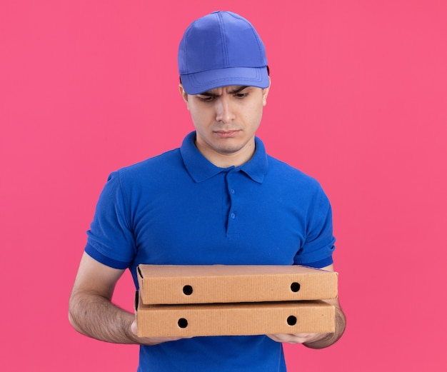 青い制服と帽子を持ってピザのパッケージを見て混乱している若い白人配達人