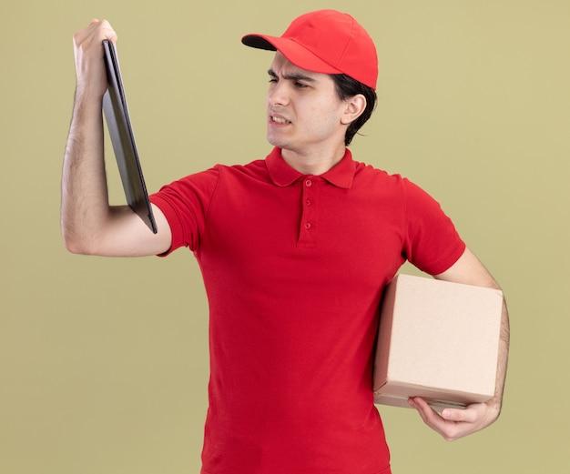 올리브 녹색 벽에 격리된 클립보드를 보고 있는 카드박스와 클립보드를 들고 있는 모자와 빨간 유니폼을 입은 젊은 백인 배달원