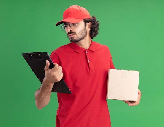 赤い制服を着た混乱した若い白人配達人とクリップボードを見てカードボックスとクリップボードを保持している眼鏡をかけているキャップ