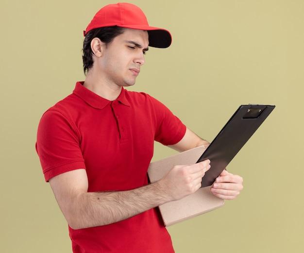 Confuso giovane fattorino caucasico in uniforme rossa e cappuccio con scatola di cartone e appunti guardando gli appunti