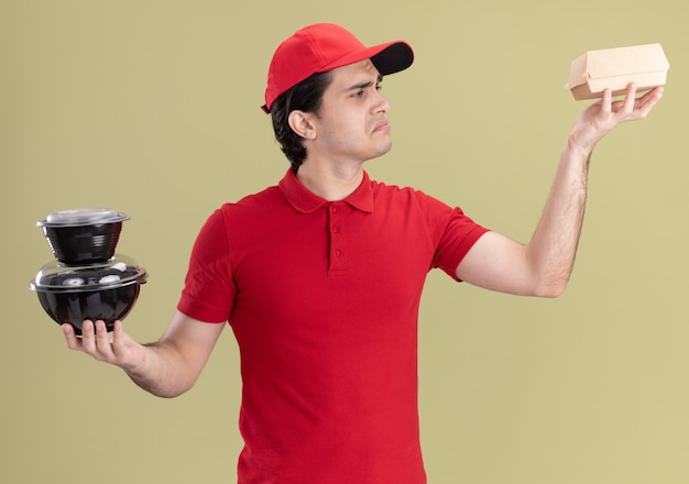 Confused young caucasian delivery man in red uniform and cap holding food containers and paper food package looking at food package