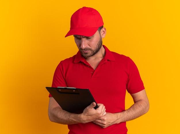 Confuso giovane fattorino caucasico in uniforme rossa e berretto che tiene e guarda la lavagna per appunti isolata sulla parete arancione