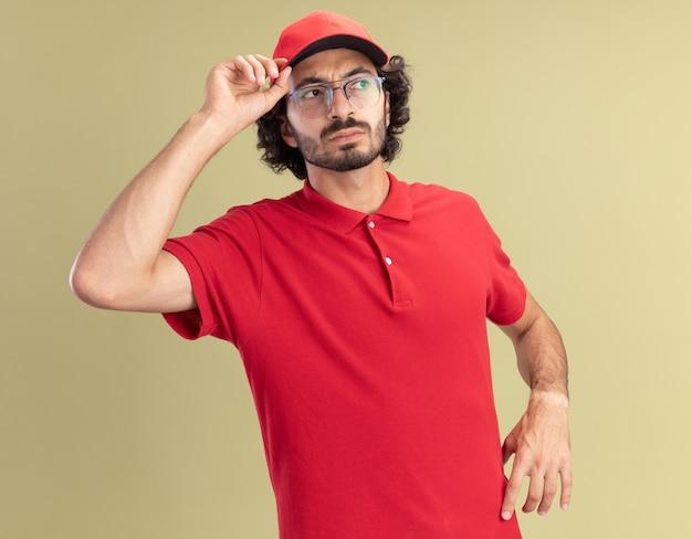 Confuso giovane fattorino caucasico in uniforme rossa e berretto con gli occhiali che afferra il berretto guardando a lato