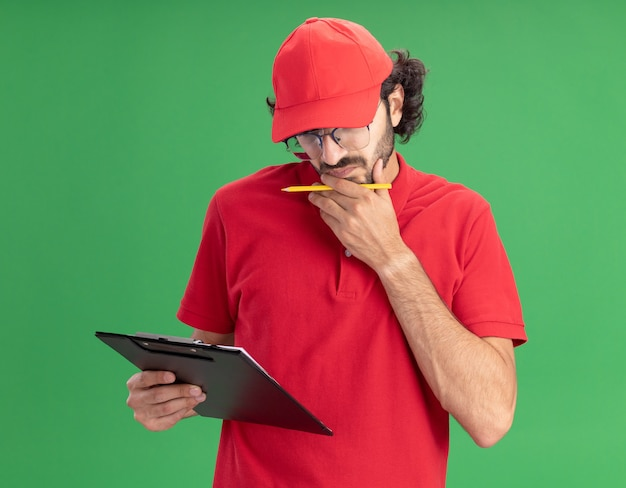 Confuso giovane fattorino caucasico in uniforme rossa e berretto con gli occhiali che tengono appunti e matita mettendo la mano sul mento guardando gli appunti isolati sul muro verde