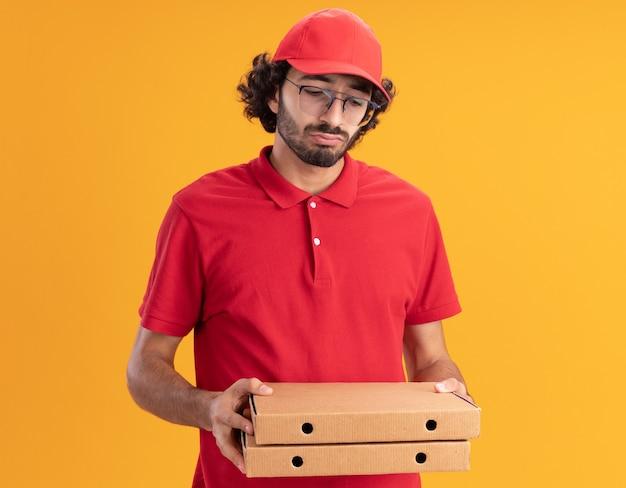 Confuso giovane fattorino caucasico in uniforme rossa e berretto con gli occhiali che tengono in mano e guardano i pacchetti di pizza