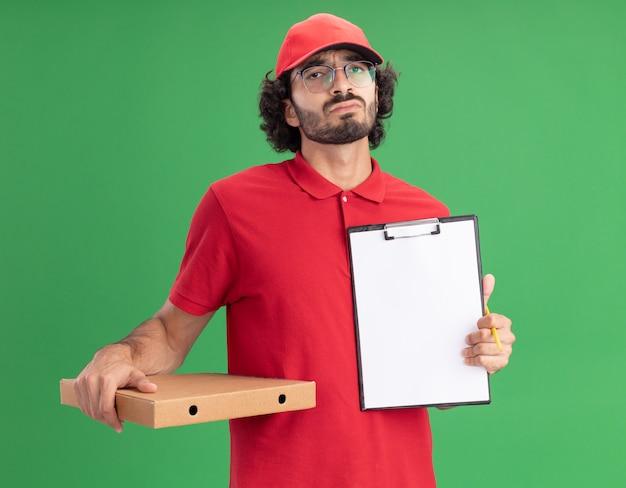 Confuso giovane fattorino caucasico in uniforme rossa e berretto con gli occhiali che tengono la matita del pacchetto di pizza che mostra gli appunti alla telecamera isolata sul muro verde