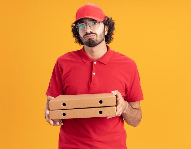 Confuso giovane fattorino caucasico in uniforme rossa e berretto con gli occhiali che tengono i pacchetti di pizza