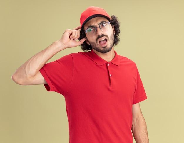 Confuso giovane fattorino caucasico in uniforme rossa e berretto con gli occhiali guardando il lato toccando la testa isolata sulla parete verde oliva