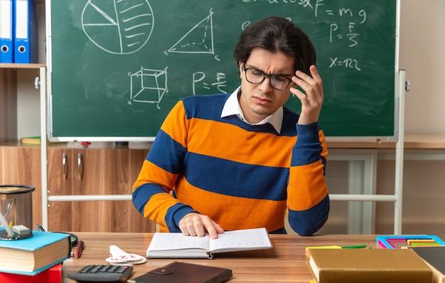 Confuso giovane insegnante di geometria caucasica con gli occhiali seduto alla scrivania con gli strumenti della scuola in classe toccando gli occhiali puntando il dito sul libro aperto leggendolo