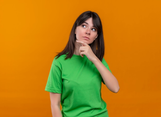 Confused young caucasian girl in green shirt puts hand on chin and looks to the side on isolated orange background