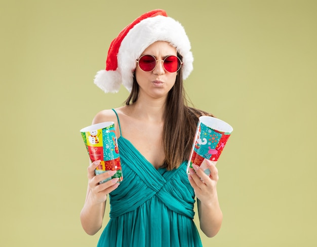 紙コップを持って見ているサンタの帽子とサングラスで混乱した若い白人の女の子