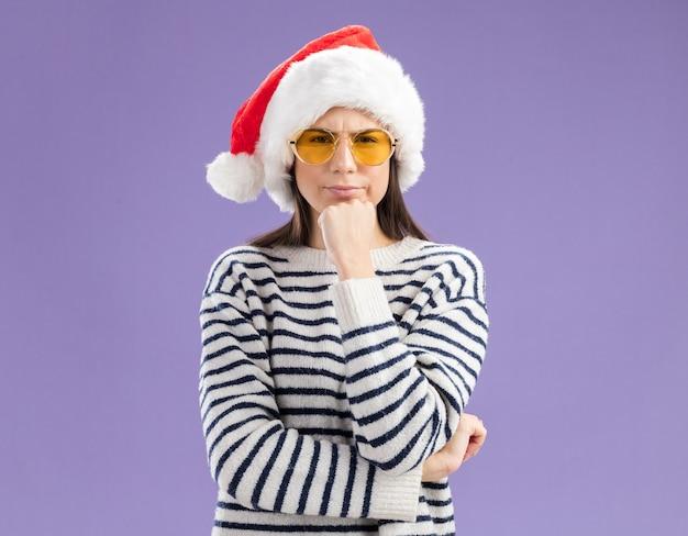 산타 모자와 태양 안경에 혼란 스 러 워 젊은 백인 여자 턱을 보유 하 고 보이는