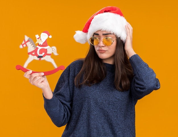 Смущенная молодая кавказская девушка в солнцезащитных очках в шляпе санта-клауса кладет руку на голову, держа и глядя на санта на украшение лошадки-качалки, изолированное на оранжевой стене с копией пространства