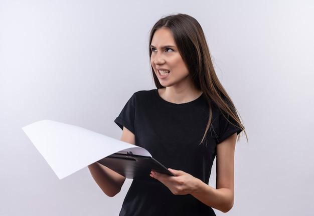 Смущенная молодая кавказская девушка в черной футболке держит буфер обмена на изолированной белой стене