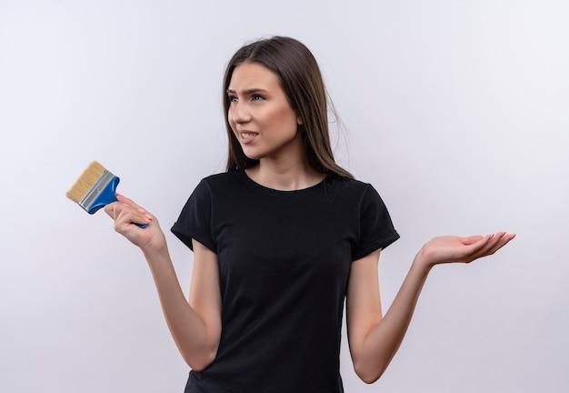 Сбитая с толку молодая кавказская девушка в черной футболке держит кисть, показывая, какой жест на изолированной белой стене