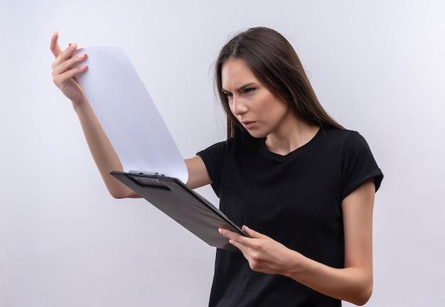 Смущенная молодая кавказская девушка в черной футболке смотрит в буфер обмена в руке на изолированной белой стене