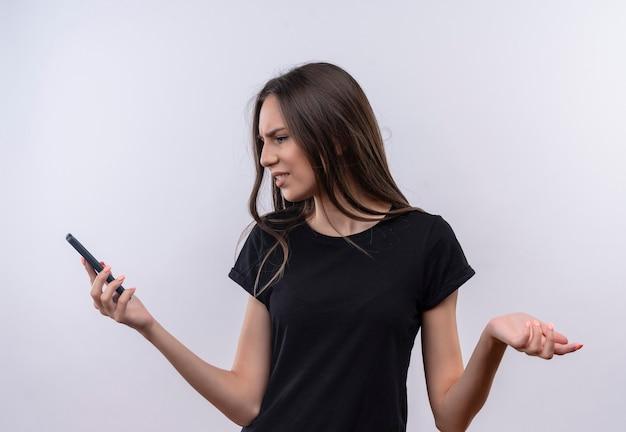 Смущенная молодая кавказская девушка в черной футболке смотрит на телефон в руке на изолированной белой стене