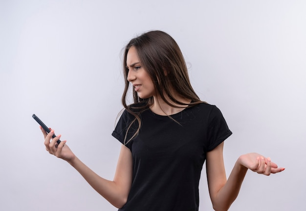 Confused young caucasian girl wearing black t-shirt looking at phone in her hand on isolated white wall