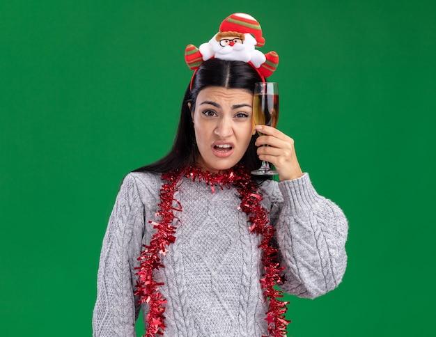 サンタクロースのヘッドバンドと首の周りに見掛け倒しの花輪を身に着けている混乱した若い白人の女の子は、緑の背景に分離されたカメラを見て、頭に触れるシャンパンのガラスを保持