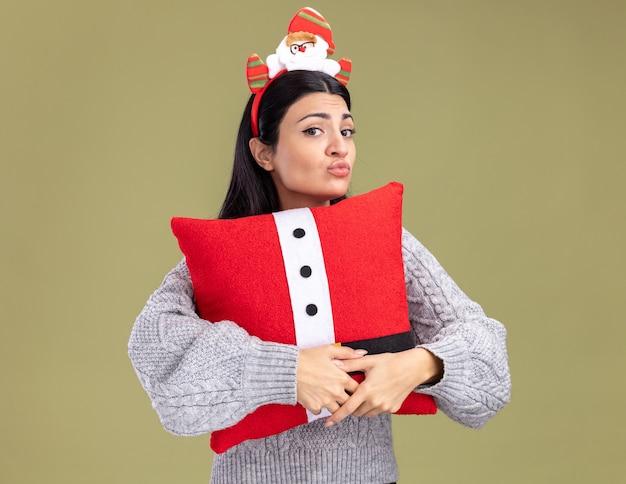 Смущенная молодая кавказская девушка в головной повязке санта-клауса обнимает подушку санта-клауса со сжатыми губами, изолированными на оливково-зеленой стене