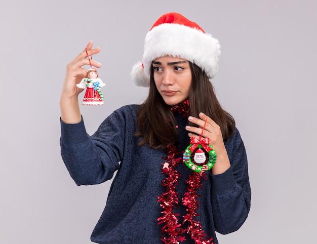 Confusa giovane ragazza caucasica con santa cappello e ghirlanda intorno al collo tiene e guarda i giocattoli dell'albero di natale isolati su sfondo bianco con spazio di copia