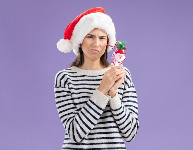 복사 공간 보라색 벽에 고립 된 사탕 지팡이 들고 산타 모자와 혼란 된 젊은 백인 여자