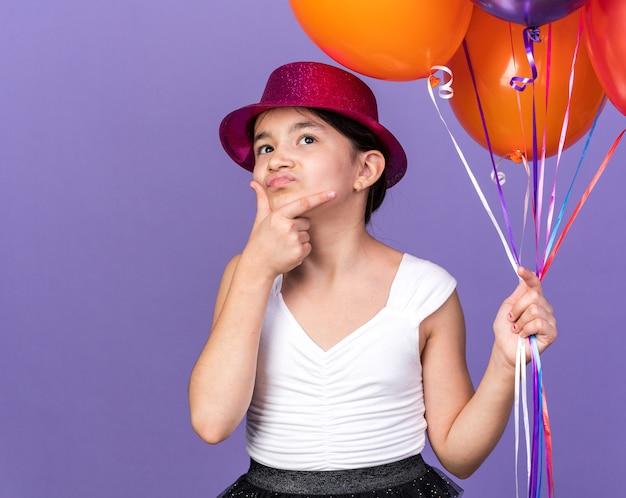 Confuso, giovane, caucasico, ragazza, con, viola, festa, cappello, presa a terra, elio, palloni, e, mettere mano, mento, osservare, su, isolato, su, viola, parete