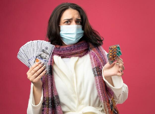 Confusa giovane ragazza malata caucasica indossando accappatoio e sciarpa con maschera che tiene soldi e confezioni di capsule mediche isolate sulla parete cremisi
