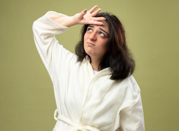 이마를 만지고 가운을 입고 혼란스러운 젊은 백인 아픈 소녀는 올리브 녹색 배경에 고립 찾고