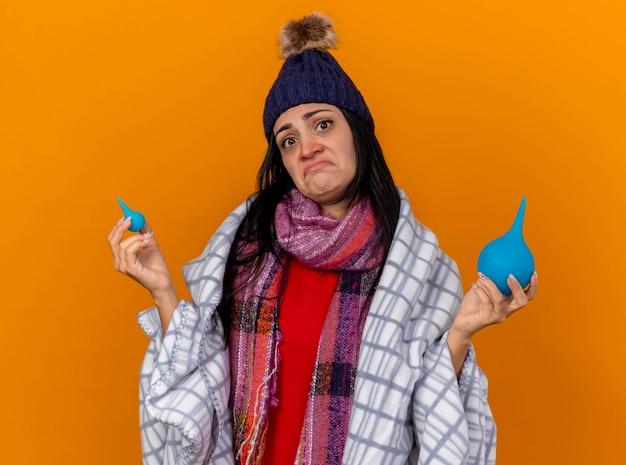 오렌지 벽에 고립 된 격자 무늬 지주 관장에 싸여 겨울 모자와 스카프를 입고 혼란 젊은 백인 아픈 소녀
