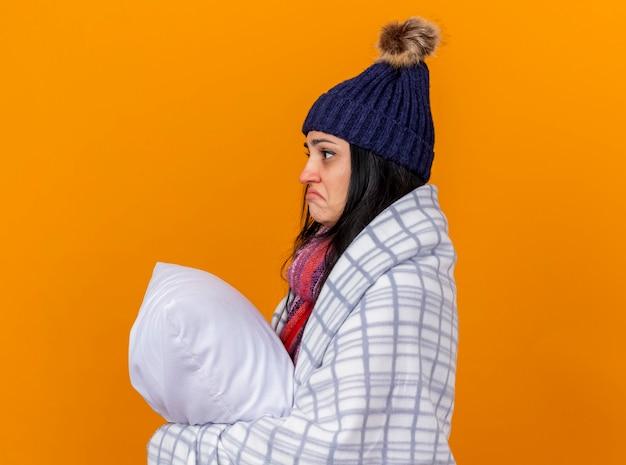 겨울 모자와 스카프를 착용하는 혼란 스 러 워 젊은 백인 아픈 소녀 복사 공간 오렌지 배경에 고립 된 똑바로 찾고 베개를 들고 프로필보기에 격자 무늬 서에 싸여