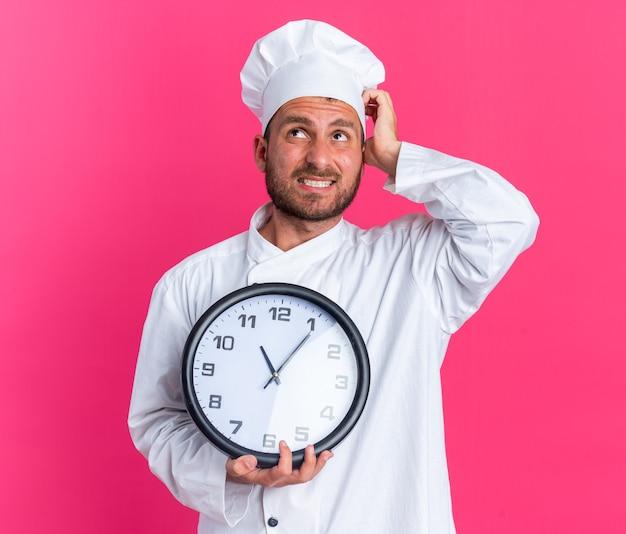 Confuso giovane maschio caucasico cuoco in uniforme da chef e cappello che tiene l'orologio guardando in alto graffiare la testa isolata sulla parete rosa