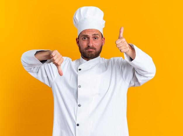 Confuso giovane maschio caucasico cuoco in uniforme da chef e berretto guardando la telecamera che mostra i pollici su e giù isolati sulla parete arancione