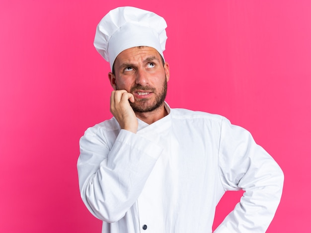 Смущенный молодой кавказский повар в униформе шеф-повара и кепке держит руку на талии и смотрит вверх на розовой стене
