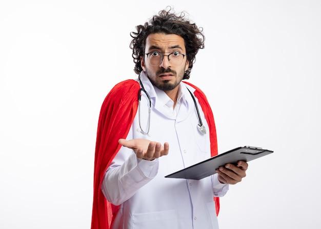 赤いマントと聴診器を首にかけた医者の制服を着た光学ガラスの混乱した若い白人のスーパーヒーローの男はクリップボードと手でポイントを保持