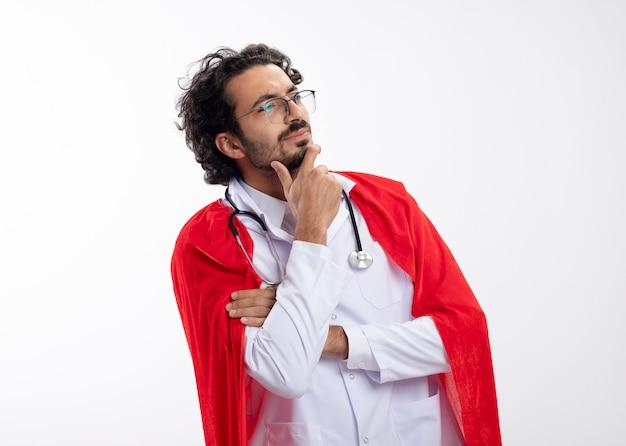 Confuso giovane supereroe caucasico uomo in occhiali ottici che indossa l'uniforme del medico con mantello rosso e con lo stetoscopio intorno al collo mette la mano sul mento guardando a lato con lo spazio della copia