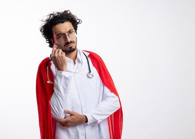 Confuso giovane supereroe caucasico uomo in occhiali ottici che indossa l'uniforme del medico con mantello rosso e con lo stetoscopio intorno al collo mette la matita sulla tempia