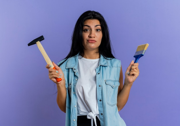 La giovane donna caucasica confusa tiene il martello e il pennello isolato su fondo viola con lo spazio della copia