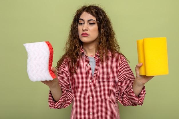 Giovane donna delle pulizie confusa che tiene e guarda le spugne per pulire