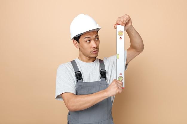 Confuso giovane operaio edile che indossa il casco di sicurezza e tenuta uniforme e guardando il righello di livello
