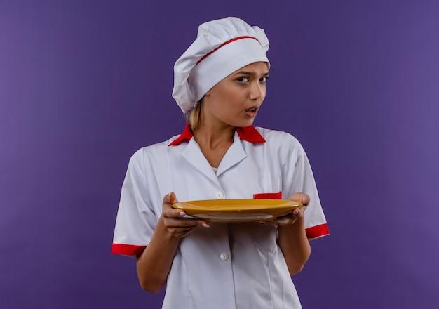 コピースペースと隔離された壁にシェフの制服保持プレートを身に着けている混乱した若い料理人の女性