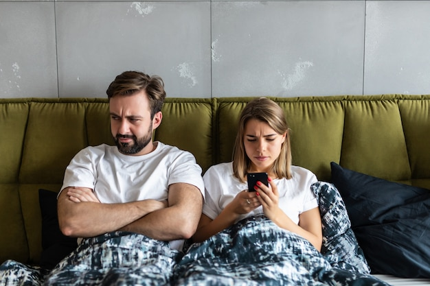 Confused young couple having an argument about mobile phone while lying in bed at home