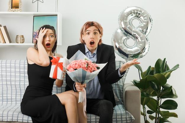 Смущенная молодая пара в счастливый женский день держит подарок с букетом, сидя на диване в гостиной