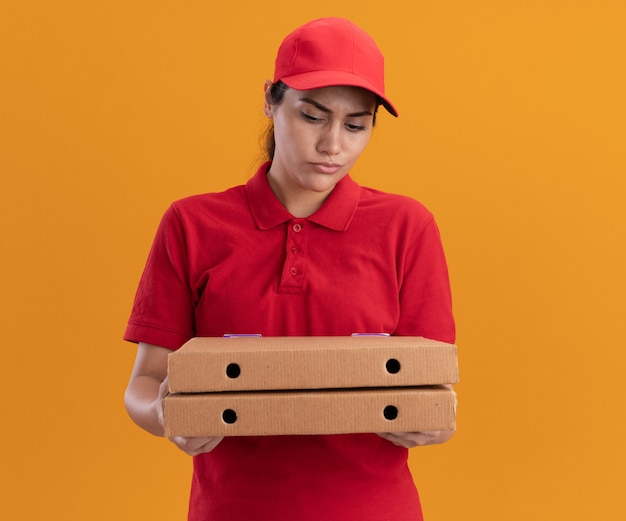Confused young delivery girl wearing uniform and cap holding and looking at pizza boxes isolated on orange wall